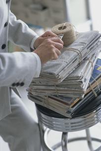新聞の束を紐で縛る手の写真素材 [FYI03368352]