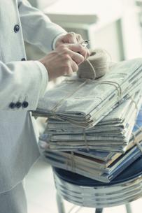 新聞の束を紐で縛る手の写真素材 [FYI03368354]