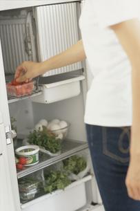 冷蔵庫からイチゴを取出す女性後姿の写真素材 [FYI03368394]