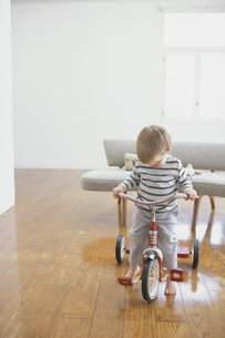 室内で三輪車をこぐ外国人男の子の写真素材 [FYI03368397]