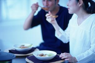 食卓に並んで食事をするカップルの写真素材 [FYI03368431]
