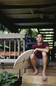 サーフボードを持って座る男性の写真素材 [FYI03368444]