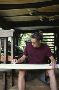 サーフボードにワックスを塗る男性の写真素材 [FYI03368445]