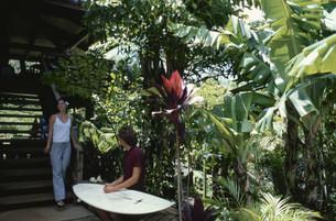 階段で話す男性サーファーと女性の写真素材 [FYI03368448]
