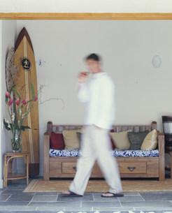 ソファの前を歩く男性の写真素材 [FYI03368477]