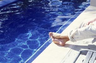 プールサイドのイスに腰掛ける男性の足元の写真素材 [FYI03368486]