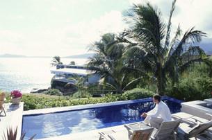プールサイドのイスに腰掛ける男性の写真素材 [FYI03368490]