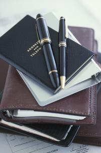 山積みになったアドレス帳と手帳とペンの写真素材 [FYI03368562]