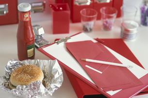 赤系ステーショナリーとハンバーガーの置かれたデスクの写真素材 [FYI03368936]
