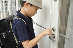玄関の鍵を開ける男の子の写真素材 [FYI03369239]