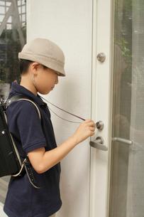 玄関の鍵を開ける男の子の写真素材 [FYI03369241]