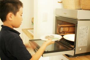 ご飯を電子レンジにかける男の子の写真素材 [FYI03369258]