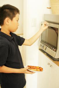 ご飯を電子レンジにかける男の子の写真素材 [FYI03369259]