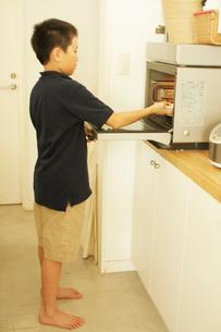 ご飯を電子レンジにかける男の子の写真素材 [FYI03369260]