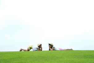 芝生にうつぶせになる2人の女の子の写真素材 [FYI03369313]