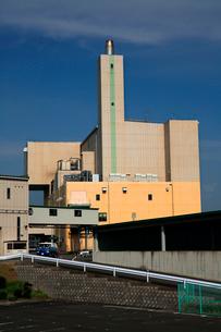青空にそびえる煙突と清掃工場の白い建物の写真素材 [FYI03369778]