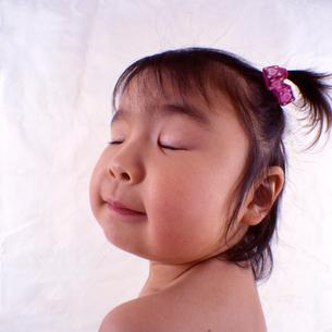 目を瞑る女の子の顔のアップの写真素材 [FYI03369828]