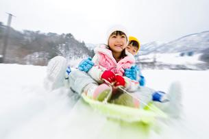 雪山でそりで遊ぶ女の子と男の子の写真素材 [FYI03369919]