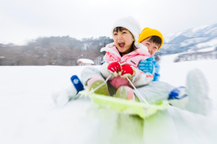 雪山でそりで遊ぶ女の子と男の子の写真素材 [FYI03369920]