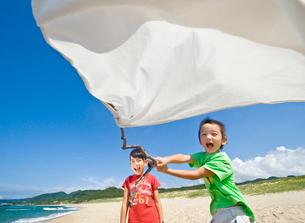 砂浜で白旗を持つ女の子と男の子の写真素材 [FYI03369924]