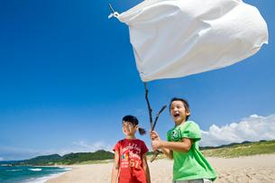 砂浜で白旗を持つ女の子と男の子の写真素材 [FYI03369927]