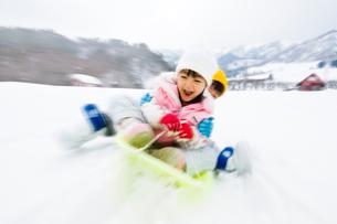 雪山でそりで遊ぶ女の子と男の子の写真素材 [FYI03369933]