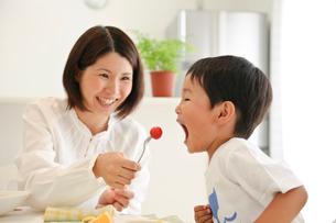 母親にトマトをもらう男の子の写真素材 [FYI03369937]