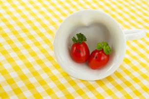顔のあるかわいいミニトマトのカップルとハート型のカップの写真素材 [FYI03370063]