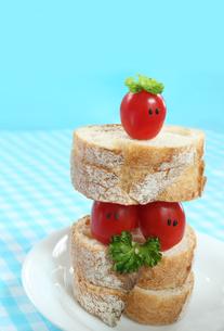 顔のあるかわいいミニトマトのカップルとパンの写真素材 [FYI03370141]
