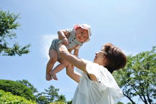 赤ちゃんを高く持ち上げる母親の写真素材 [FYI03370160]