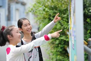 掲示板を見てる女の子の写真素材 [FYI03370162]