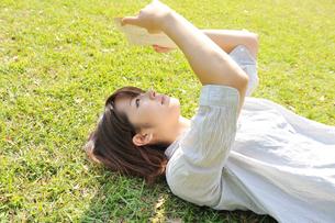 芝生に寝転び本を読んでいる女性の写真素材 [FYI03370165]