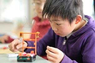 電磁石にクリップを付けている小学生の写真素材 [FYI03370186]