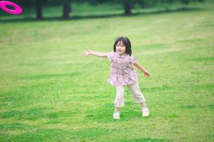 公園でフリスビーをする女の子の写真素材 [FYI03370332]