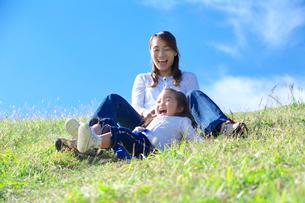 土手滑りをして遊ぶ親子の写真素材 [FYI03370345]