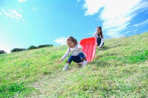 土手滑りをして遊ぶ親子の写真素材 [FYI03370347]