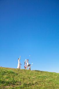 土手で紙飛行機を飛ばす親子の写真素材 [FYI03370357]