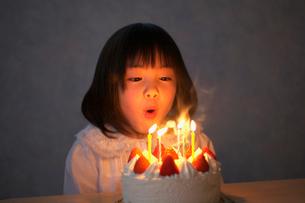 ケーキのろうそくを吹き消す女の子の写真素材 [FYI03370361]