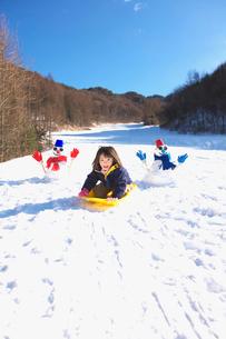 ソリで雪滑りをする女の子の写真素材 [FYI03370413]