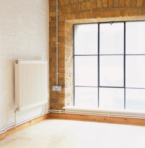 部屋のコーナーにあるヒーターと窓の写真素材 [FYI03375047]