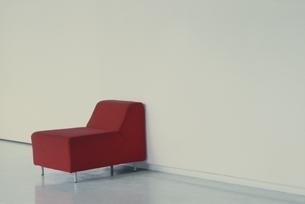 白い壁の前に置かれた赤いソファの写真素材 [FYI03376532]