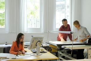 オフィスの女性と2人の男性の写真素材 [FYI03378324]