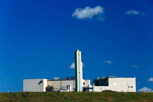 白い雲が浮かぶ青空の下、煙突がそびえる清掃工場の白い岳物の写真素材 [FYI03378392]