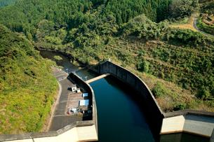 秋の季節、水の貯水を制限しながら放水するダムの管理所の写真素材 [FYI03378431]