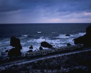 冬の海岸をゆく五能線の写真素材 [FYI03379437]