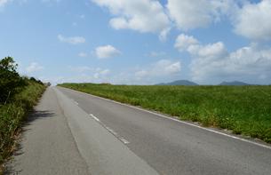 草原の横に伸びる直線の一本道の写真素材 [FYI03386598]