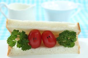 顔のあるかわいいミニトマトのカップルとパンの写真素材 [FYI03386652]