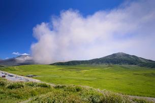 噴煙上げる阿蘇中岳と草千里の写真素材 [FYI03389070]