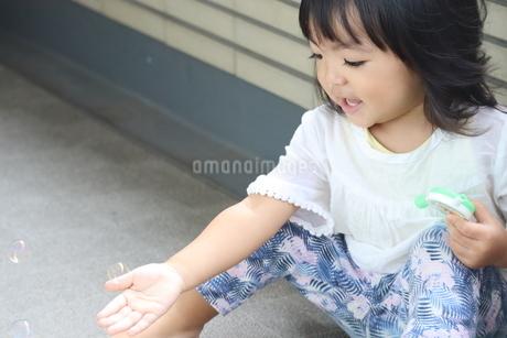 シャボン玉をさわろうとしている女の子の写真素材 [FYI03389104]