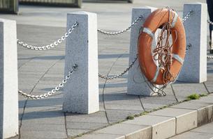 港の岸辺の救命浮き輪の写真素材 [FYI03391435]